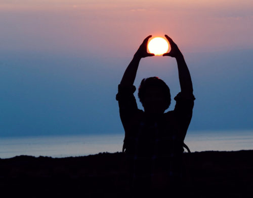 Man in darkness with hands help up to surround the sun