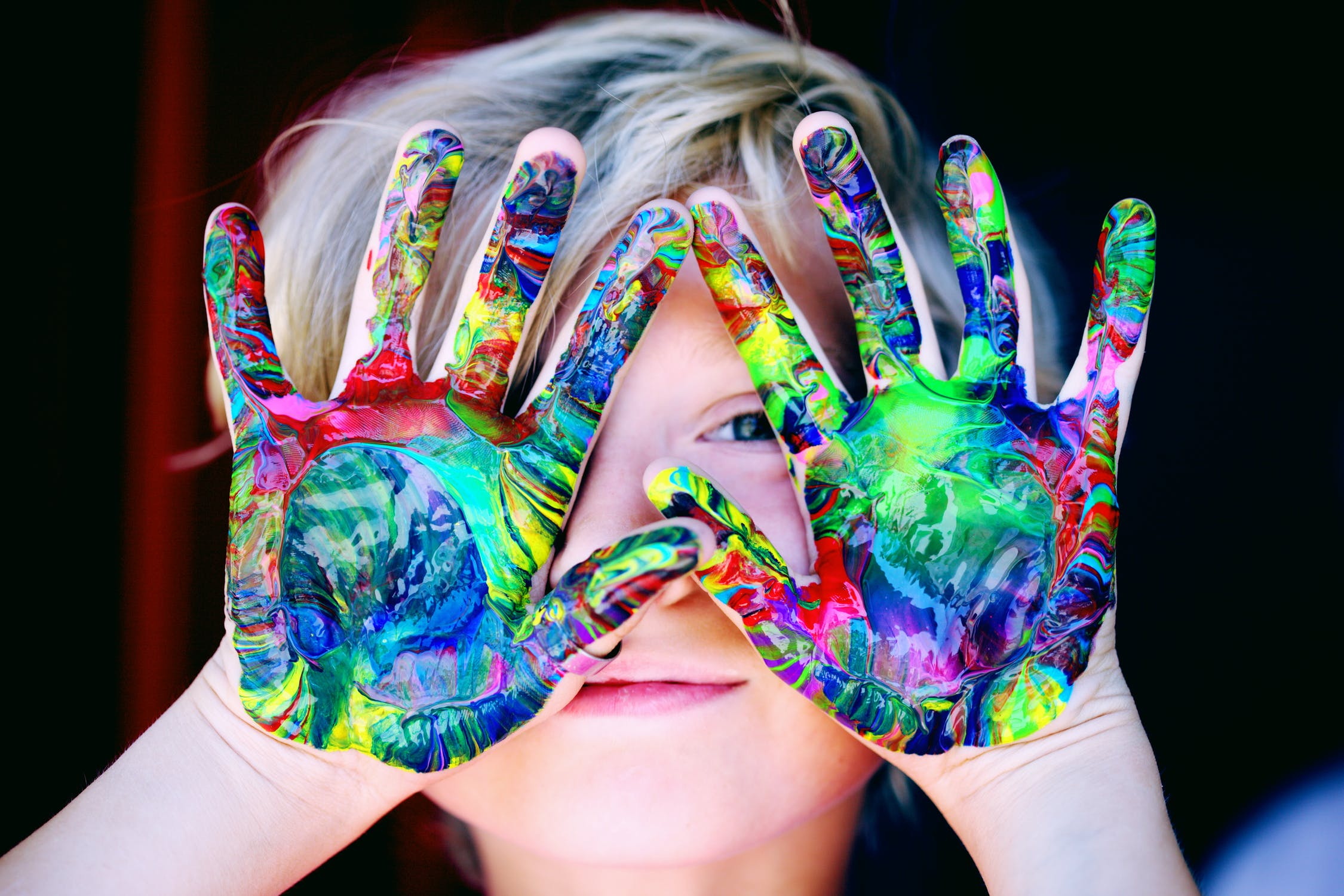young child covering face with hands dirty from multicolor paint
