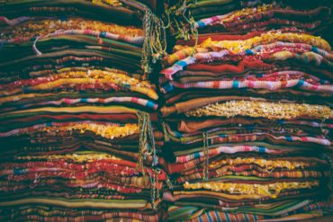 72d5483d9 stacks of brightly colored fabric stacked high
